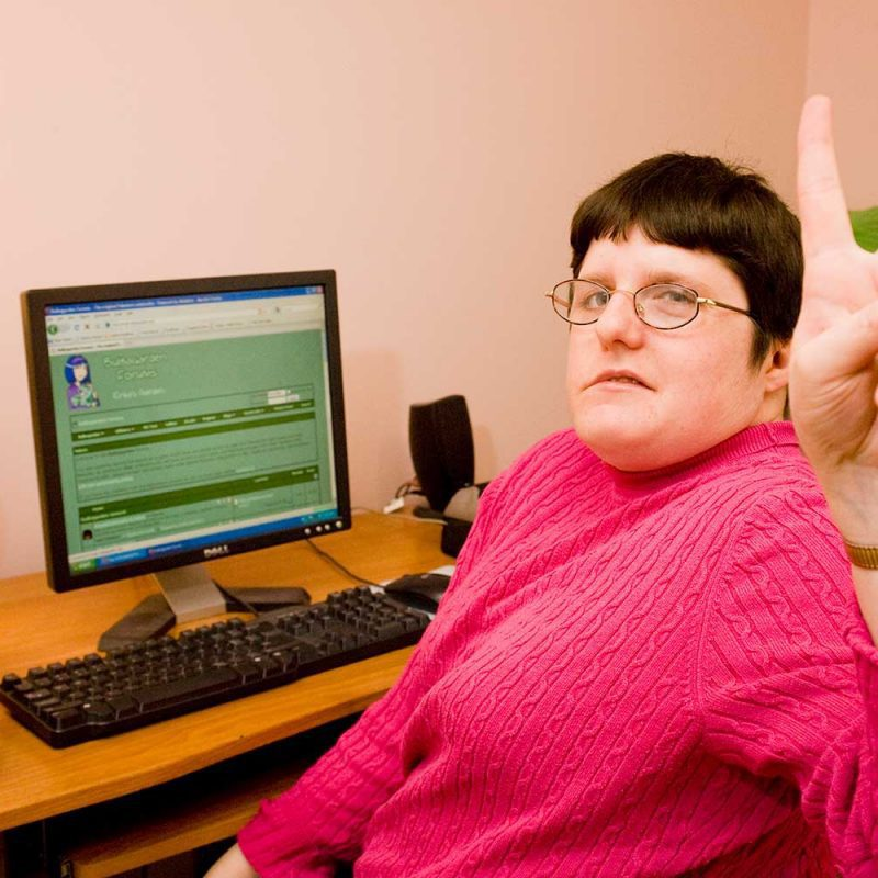 client using a computer giving the peace sign